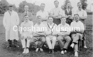 Eleven men appear to be a cricket team. One man wears white umpire's coat. Possibly Wilfred Cox (third from right, seated). 1930s or 1940s. Photo courtesy of Norman Baines. [image code: h6-25-02]