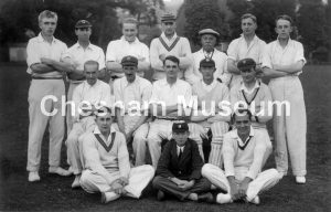 Fourteen men and a school boy. All the men are wearing whites, some wear caps and one wears cricket pads. 1930s or 1940s. Photo courtesy of Norman Baines. [image code: h6-25-03]