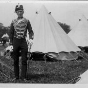 soldier standing in front of a camp of tents