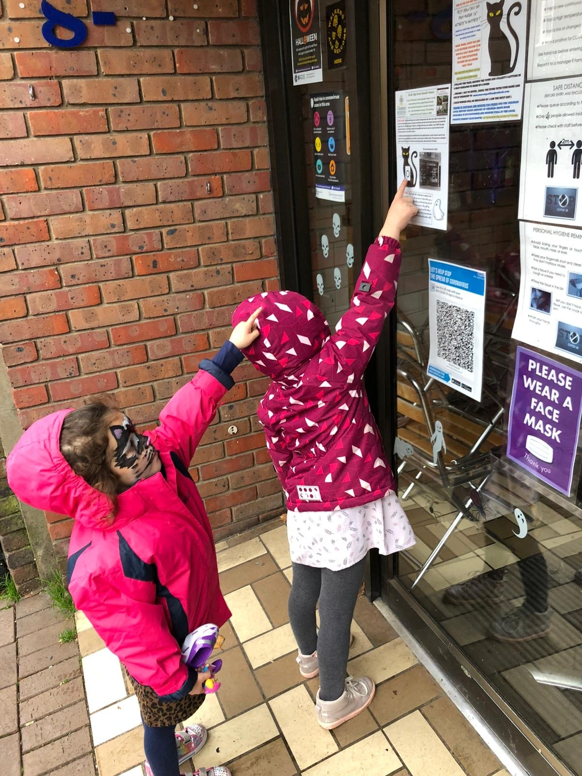 2 children pointing at the museum's spooky shop trail in a shop window