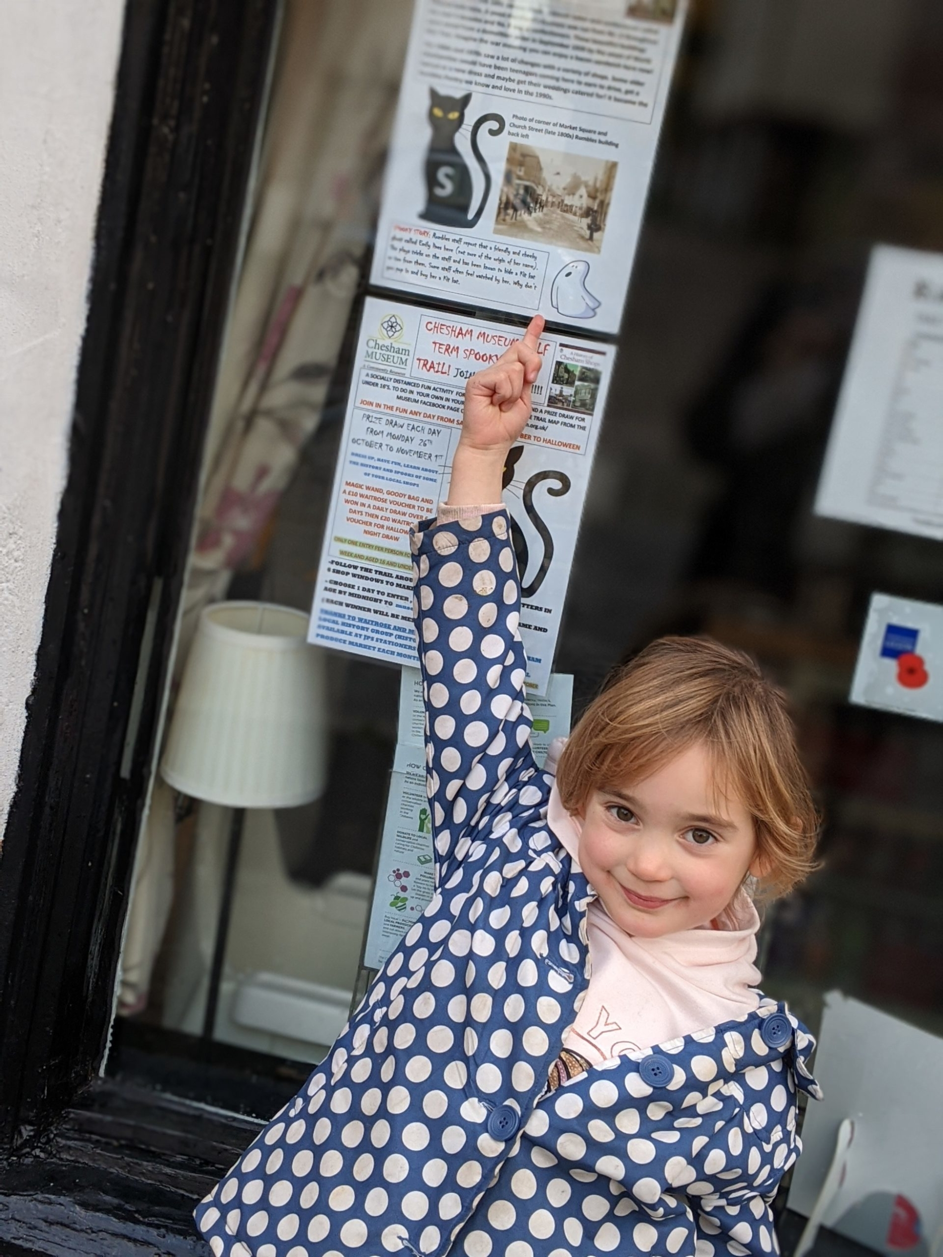 Ellie pointing at poster in shop window