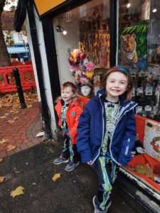 Summer and Charlie standing outside a shop window.