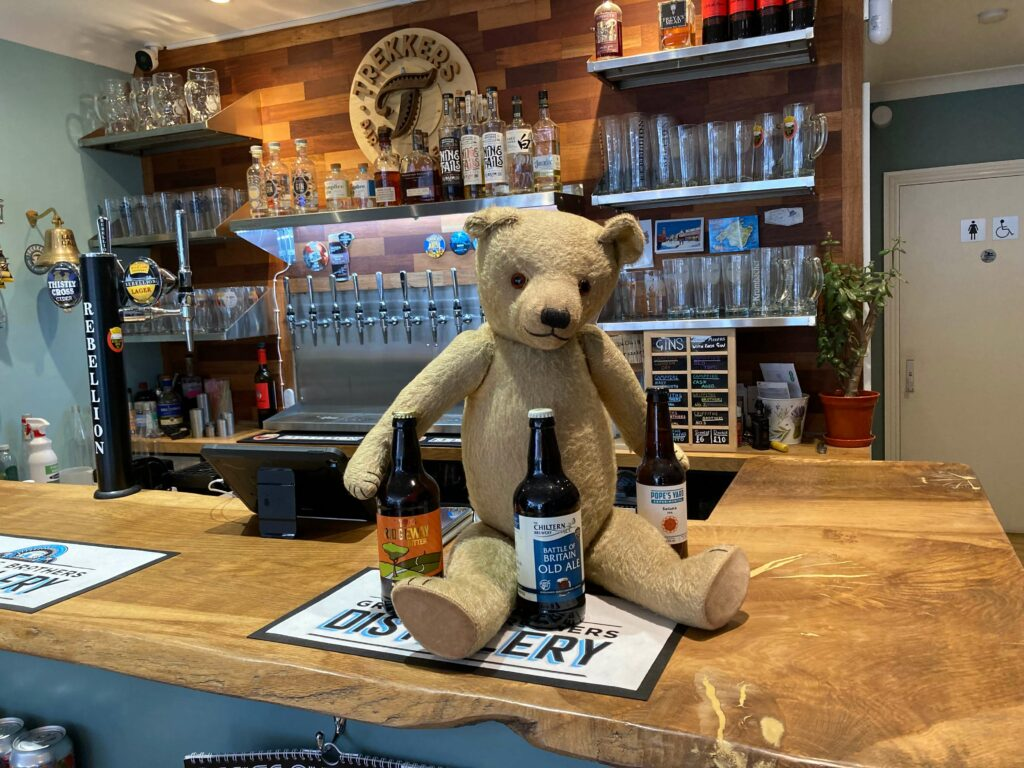 Teddy at the bar with three bottles of ale/bitter next to them