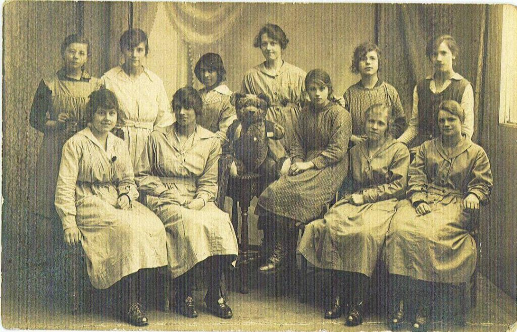 Teddy on a stool surrounded by women